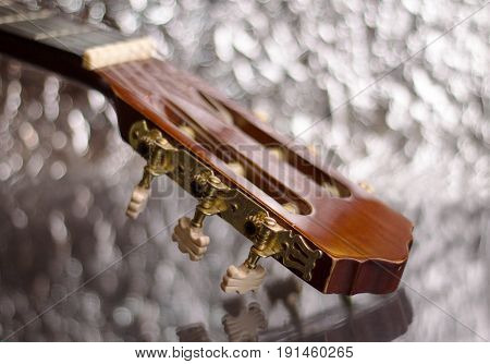 Guitar headstock on silver background, close up, focus on headstock