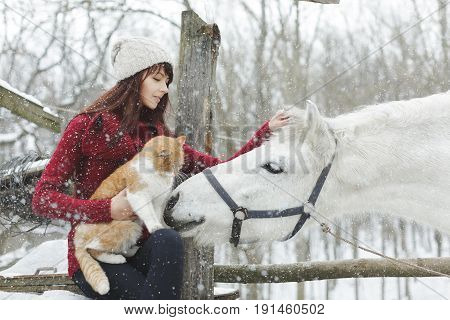 Happy young people on countryside with horse for riding. Pretty brunette young woman with a white horse riding in winter. Young woman hugging her horse.