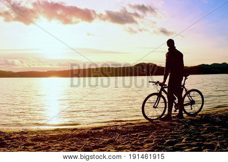 Young Man Cyclist Silhouette On Blue Sky And Sunset Above The Beach. Biker Atthe End Of Season At La