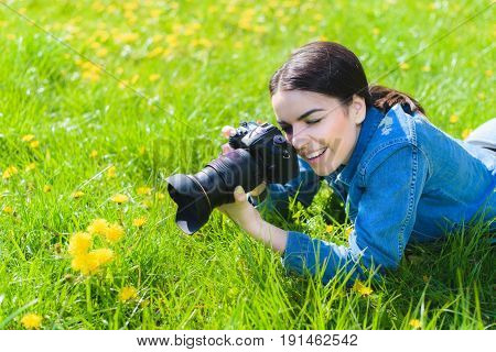 Attractive Girl In A Meadow Takes Pictures Of Flowers