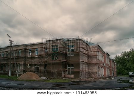 Dark gloomy double-storey house under a cloudy sky.