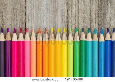 Colorful pencil crayon on a weathered wood background with copy space