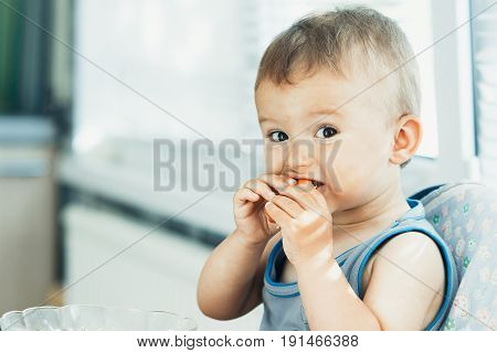 The child is sitting in the kitchen and greedily eats sausage