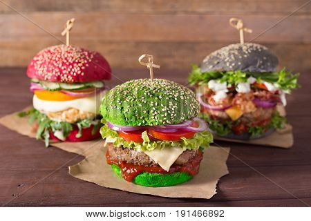 Three burgers with different bread buns on nice wood background
