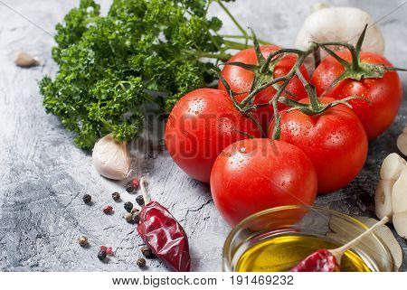 Ripe cherry tomatoes on a branch linseed oil curly parsley garlic and spices on a concrete background. Top view Copy space.