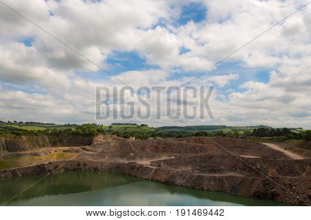 Quarrying operations at Wick Quarry. Machinery engaged in limestone aggregate mining and crushing near Bristol with English countryside and bright sky