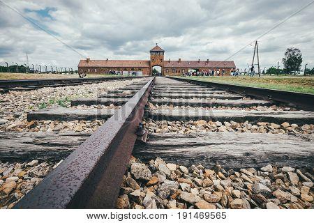 Oswiecim Poland - June 14 2017: Auschwitz-Birkenau concentration camp main gate with railway track on June 14 2017 in Oswiecim Poland.