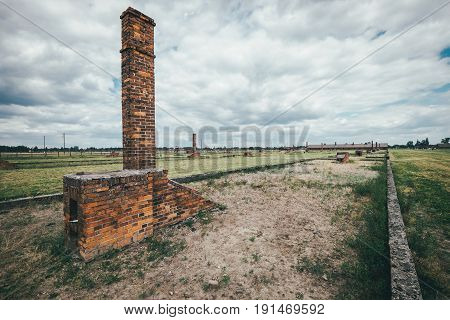 Oswiecim Poland - June 14 2017: Auschwitz-Birkenau concentration camp burnt wooden barracks remains on June 14 2017 in Oswiecim Poland.