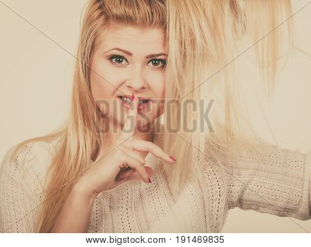 Woman Holding Her Blonde Hair Showing Silence Gesture