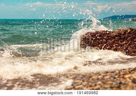 Breaking big waves sunlit sea foam in summer
