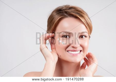 Beauty and skincare concept. Young woman applying moisturizer on face. Beautiful girl applying cosmetic cream on skin near eyes.