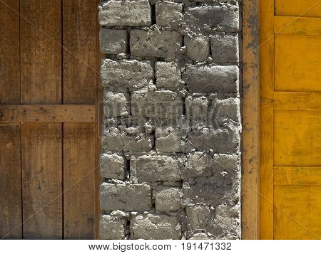 Brick wall between the wooden doors: on the left is an old brown door on the right is a bright yellow door a modern stone and wood texture.
