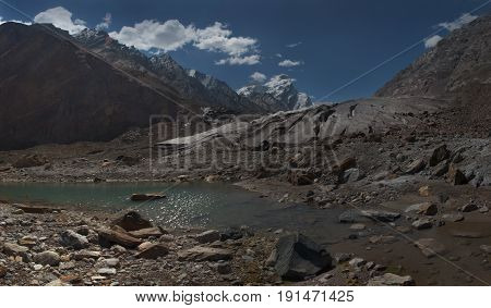 Huge high mountains glacier of the Himalayas: powerful brown moraines of the sediments descend from the mountainous icy peaks the foreground is an elongated lake with muddy gray water photopanorama Northern India.
