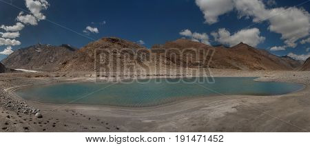 A beautiful glacial lake with a turquoise surface of clear water in the middle of the moraine surrounded by the high mountains of the Himalayas patterns of white clouds on a bright blue sky Zanskar Northern India.