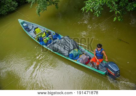 CUYABENO, ECUADOR - NOVEMBER 16, 2016: Unidentified man travelling by boat into the depth of Amazon Jungle in Cuyabeno National Park, Ecuador.