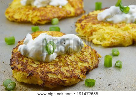 Spaghetti squash fried cakes with sour cream and green onions on a metal board