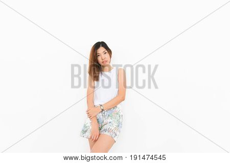 an asian girl with white undershirt and shorts is posing on the white background