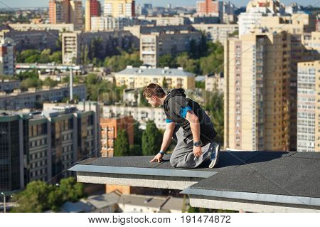 Roofer on the edge of the roof. A man looks down from a high-rise building. Courage and adrenaline. Roofing.