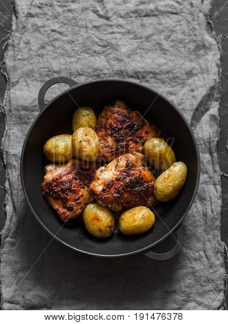 Roasted harissa chicken and new potatoes in a cast iron skillet on a dark background top view
