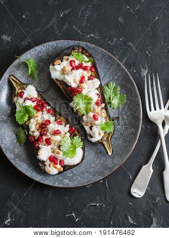 Grilled eggplant with feta pomegranate pine nuts and cilantro. Delicious appetizer or snack on a dark background top view