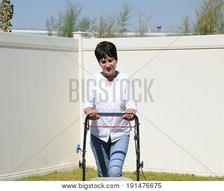 Mature female beauty mowing her lawn outside.