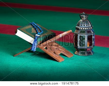 still life image of the Quran. The Quran literally meaning 'the recitation' is the central religious text book of Islam which Muslims believe to be the verbatim word of God or Allah