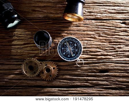 compass and flashlight placed on wooden background equipment for travel and expedition