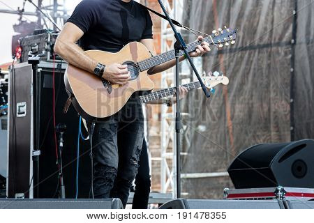 Musician Playing Acoustic Guitar On Outdoor Stage During Live Concert