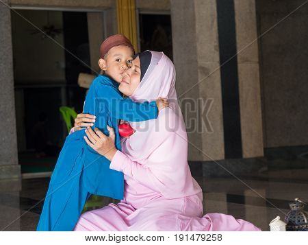 happy muslim kid with full dress kiss his mother asian traditonal style dress