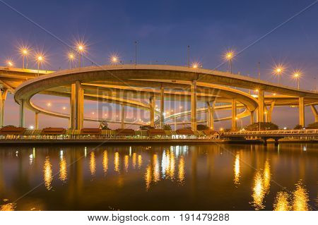 Blue twilight sky over round highway intersection river front and reflection Bangkok Thailand