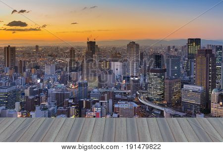 Opening wooden floor Sunset over Osaka busienss downtown with mountain background Japan