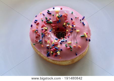 Pink strawberry iced doughnut with sprinkles on a white plate