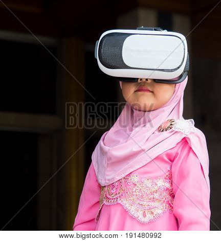 happy muslim girl with full hijab in pink dress asian traditional style dress playing VR box with mobile smart phone