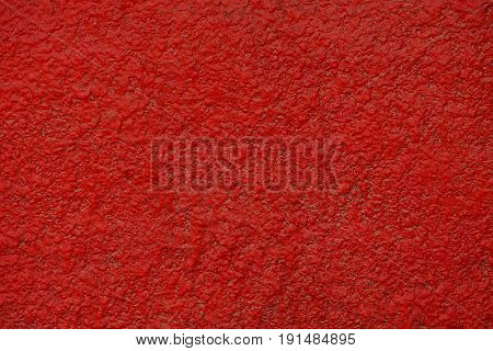 Bright red background of a piece of concrete wall of a building