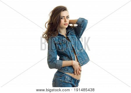 beautiful brunette in jeans jacket erotic poses in the Studio and looking at camera isolated on white background