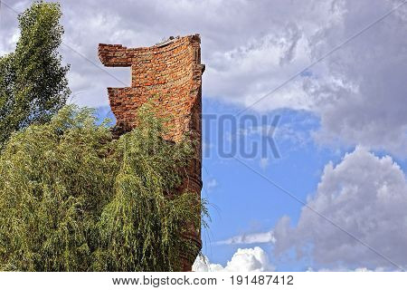 Ruined brick water tower with part of the wall and tree branches against the sky