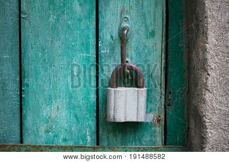 Vintage hanging lock, closed green wood door. Selective focus photo.