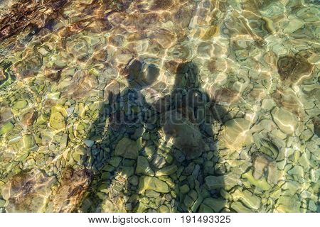 Shadow of young couple in water on rocky beach