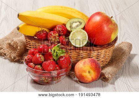 Fresh Strawberries  In The Glass Bowl, Nectarine, Lime, Kiwi, Banana, Apple In A Wicker Basket On Th