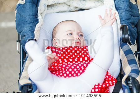 Photo of adorable baby girl laying in pram