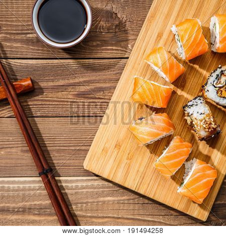 Sushi on wooden board at table with chopsticks and soy sauce