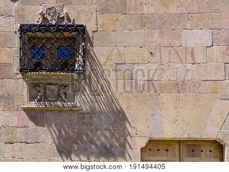 Window with bars on Facade of the Casa de las Conchas in Salamanca, Spain. exterior image shot from public floor. The Old city of Salamanca is declared by UNESCO a World Heritage Site.