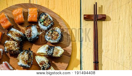 Photo of Japanese rolls on wooden board at unpainted table