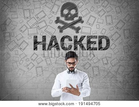 Businessman using dital tablet in front of wall with skull and crossbones icon, hacked computer concept