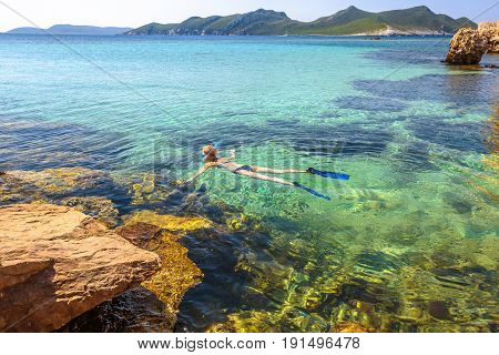 Female bikini snorkeling around Methoni Castle, a medieval fortification in Methoni, Messenia, Peloponnese, Greece. Woman snorkeler swims in crystal water and roks. Nature scenic landscape.
