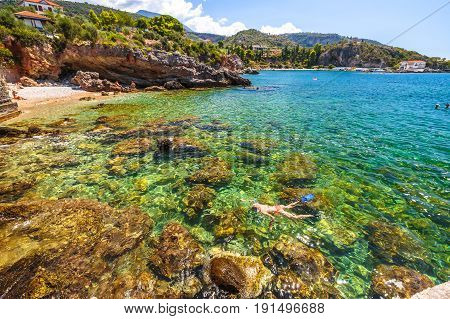 Woman snorkeling in Foneas Beach, Kardamili, Peloponnese. Female bikini snorkeling around the rocks in summer. Woman snorkeler swims in crystal water. Nature scenic landscape in Mani Peninsula, Greece