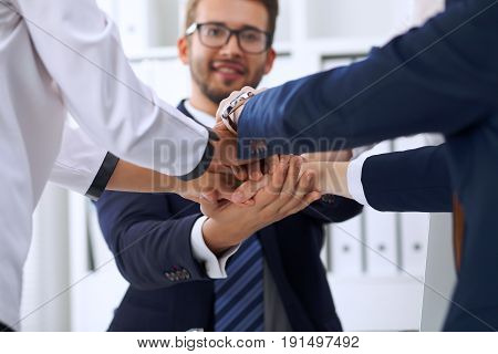 Business people group happy showing teamwork and joining hands or giving five after signing agreement or contract in office. Success concept.