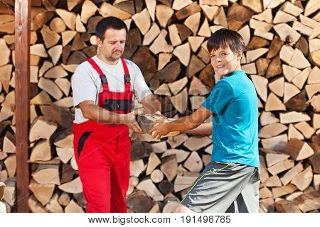 Teenage boy helping father stack the firewood - handing him the wooden blocks