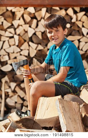 Teenage boy sitting on heap of firewood preparing to chop and stack it in a woodshed