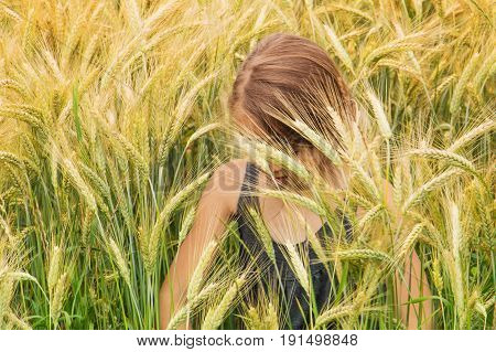Little girl submerged under the spikes of a ripening grain field looking down